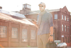 Young urban businessman professional on smartphone walking Stock Photos