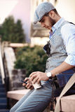 Young urban businessman professional on smartphone. Walking in street using app texting sms message Royalty Free Stock Photos