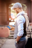 Young urban businessman professional on smartphone. Walking in street using app texting sms message Royalty Free Stock Photo