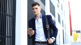 Young urban businessman professional on smartphone walking in street using mobile phone. Royalty Free Stock Image