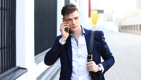 Young urban businessman professional on smartphone walking in street using mobile phone. Royalty Free Stock Photography