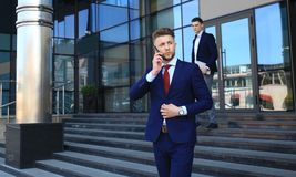 Young urban businessman professional on smartphone walking in street using mobile phone. Stock Images