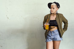Young urban girl in short shorts holding drink. Young urban girl, on grungy background holding juice with straw Royalty Free Stock Photos