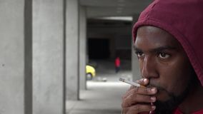 Young Urban Male Smoking. Stock video of an African American man stock footage