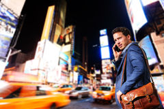 Young urban professional business man in New York. Young urban professional business man talking on smart phone onTimes Square, Manhattan, New York City. Young stock image