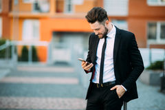 Young urban professional man using smart phone. Businessman holding mobile smartphone using app texting sms message. Young professional man using smart phone Stock Photo