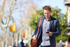 Young urban professional man using smartphone app. Young urban businessman professional on smartphone walking in street using mobile phone app texting sms Royalty Free Stock Images