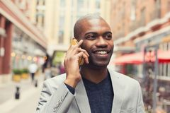 Young urban professional smiling man using smart phone Royalty Free Stock Photos