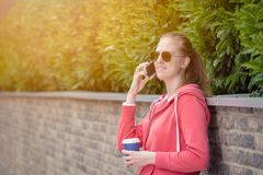 Portrait of young female making a call by using smartphone and h stock image