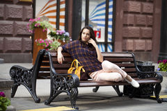 Young urban woman sits on a bench Royalty Free Stock Photo