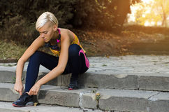 Young urban woman, tying shoelace preparing for running stock photography