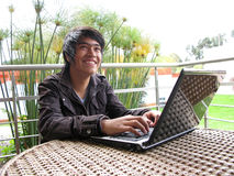 Young using laptop outdoors Stock Images