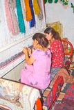 Young Uzbek girls weave carpet Stock Images