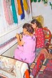Young Uzbek girls weave carpet. Young Uzbek girls in colorful national costumes weave carpets,  Samarkand Stock Images
