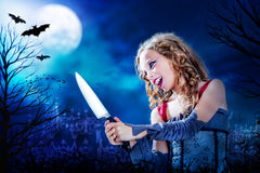 Young vampire with knife at full moon. Close up horror portrait of Young female vampire holding big knife at dusk.Full moon and flaying bats over graveyard in Royalty Free Stock Photography