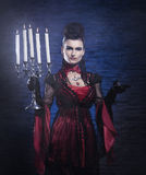 A young vampire lady in a dress holding candles Royalty Free Stock Image