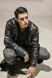 Young Vampire Man with Black Leather Jacket. Portrait of a Young Vampire Man with Black Leather Jacket Sitting on Floor Royalty Free Stock Images