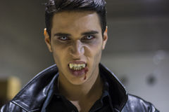 Young Vampire Man Face with Blood on his Mouth. Close up Face of a Handsome Vampire Man in Leather Clothing, with Blood on his Mouth, Looking at the Camera Royalty Free Stock Image