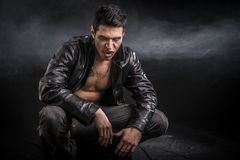 Young Vampire Man in an Open Black Leather Jacket. Portrait of a Young Vampire Man in an Open Black Leather Jacket, Showing his Chest and Abs, Looking at the Stock Image