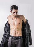Young Vampire Man in an Open Black Leather Jacket. Portrait of a Young Vampire Man in an Open Black Leather Jacket, Showing his Chest and Abs, Looking at the Royalty Free Stock Image
