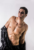 Young Vampire Man in an Open Black Leather Jacket. Portrait of a Young Vampire Man in an Open Black Leather Jacket, Showing his Chest and Abs, Looking at the Stock Images