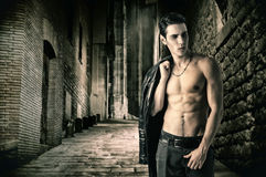 Young Vampire Man in an Open Black Leather Jacket. Portrait of a Young Vampire Man in an Open Black Leather Jacket, Showing his Chest and Abs, Looking to Right Stock Image