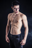 Young Vampire Man Shirtless, Gesturing to Camera. Portrait of a Young Vampire Man Shirtless, Showing his Torso, Chest and Abs, Looking at the Camera, on Dark Stock Image