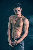 Young Vampire Man Shirtless, Gesturing to Camera. Portrait of a Young Vampire Man Shirtless, Showing his Torso, Chest and Abs, Looking at the Camera, on Dark Royalty Free Stock Image