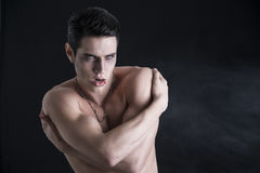 Young Vampire Man Shirtless, Gesturing to Camera. Portrait of a Young Vampire Man Shirtless, Showing his Torso, Chest and Abs, Looking at the Camera, on Dark Stock Photos