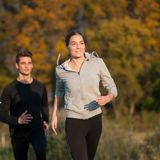 Young  veautiful couple runs on a path in park on autumn. Afternoon Royalty Free Stock Photos