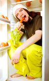 Young vegetarian. Young man sitting in the fridge and nibbling a carrot royalty free stock photos