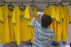 Young Vendor Arranging Brazil Shirts at Market Stock Images