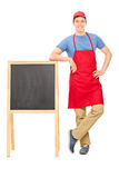 Young vendor standing by a blackboard Royalty Free Stock Photos