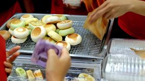 Young vendors selling freshly baked custard bread to a customer. stock footage