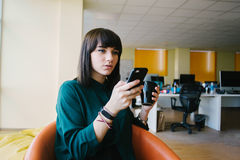 Young and very beautiful business woman uses phone and holding a cup of coffee. Against the background of office jobs. Break in the modern office Stock Photos
