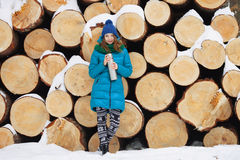 Young very positive woman in coat blue funny knitted hat posing with thermos in winter forest park against big logs. Winter active Stock Photography
