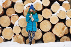 Young very positive woman in coat blue funny knitted hat posing with thermos in winter forest park against big logs. Winter active Stock Images