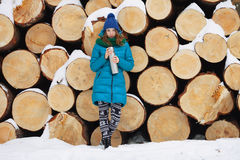 Young very positive woman in coat blue funny knitted hat posing with thermos in winter forest park against big logs. Winter active Royalty Free Stock Photography