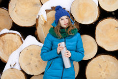 Young very positive woman in coat blue funny knitted hat posing with thermos in winter forest park against big logs. Winter active Stock Image