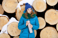 Young very positive woman in coat blue funny knitted hat posing with thermos in winter forest park against big logs. Winter active Royalty Free Stock Photo