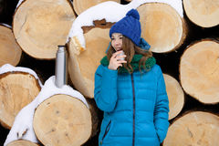 Young very positive woman in coat blue funny knitted hat posing with thermos in winter forest park against big logs. Winter active Stock Photos