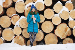Young very positive woman in coat blue funny knitted hat posing with thermos in winter forest park against big logs. Winter active Royalty Free Stock Photos