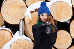 Young very positive woman in sweater blue funny knitted hat posing with dslr camera in winter forest park against big logs. Winter Stock Photography
