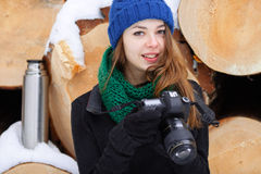 Young very positive woman in sweater blue funny knitted hat posing with dslr camera in winter forest park against big logs. Winter Royalty Free Stock Photography