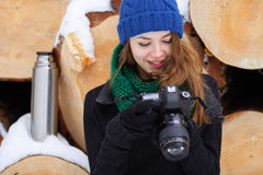 Young very positive woman in sweater blue funny knitted hat posing with dslr camera in winter forest park against big logs. Winter Stock Images