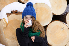 Young very positive woman in sweater blue funny knitted hat posing with thermos in winter forest park against big logs. Winter act Stock Photo