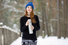 Young very positive woman in sweater blue funny knitted hat posing with thermos in winter forest park. Winter active leisure fresh Royalty Free Stock Photo