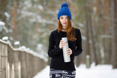 Young very positive woman in sweater blue funny knitted hat posing with thermos in winter forest park. Winter active leisure fresh Royalty Free Stock Photography