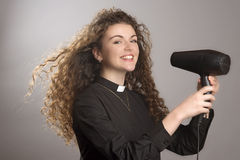 Young vicar blow drying her long hair Royalty Free Stock Photos