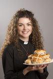 Young vicar with traditional Hot Cross buns Royalty Free Stock Photography